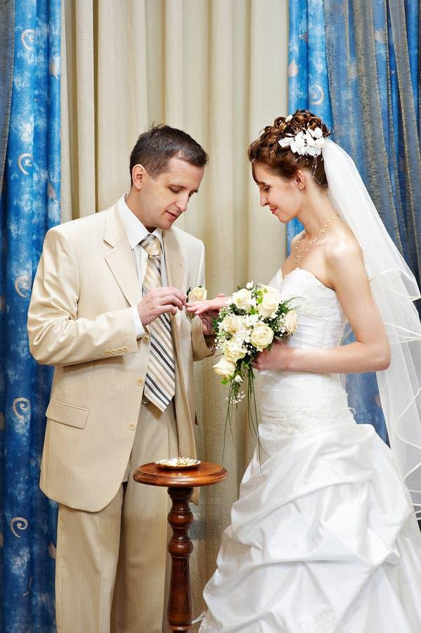 Bräutigam trägt einen Hochzeitsring eine glückliche Braut stockbilder