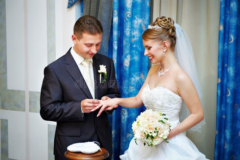 Bräutigam trägt glückliche Braut des Hochzeitsringes lizenzfreies stockbild