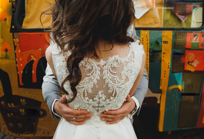 Bräutigam umarmt Braut im eleganten weißen Satinkleid mit gestickter Spitze zurück Bunter Hippiebus auf Hintergrund Deutschland-M lizenzfreies stockbild