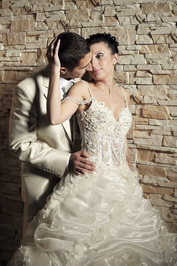 Bräutigam und Braut nahe der Backsteinmauer stockbilder