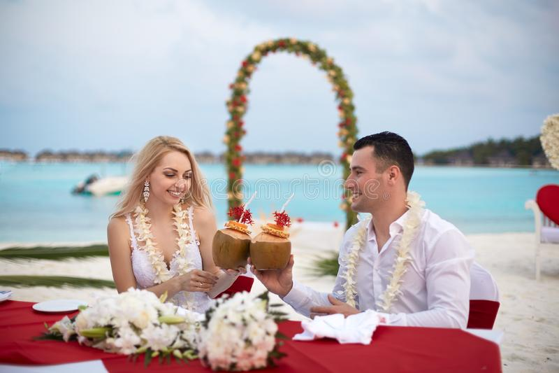 Bräutigam und Braut trinken Kokosnusscocktails an der Hochzeitstafel mit Leu Blumen auf dem Strand von Tropeninsel auf Malediven lizenzfreie stockbilder