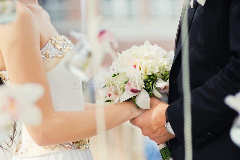 Bräutigam und Braut während der Hochzeitszeremonie, Abschluss oben auf Händen Hochzeitspaare und Hochzeitszeremonie im Freien stockfotos