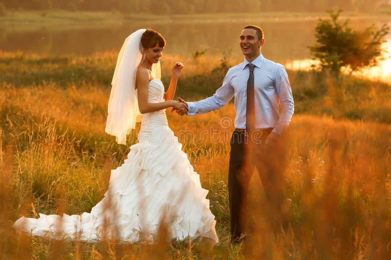 Bräutigam und Braut wirft auf dem schönen Sonnenuntergang O des Hintergrundes auf stockbild