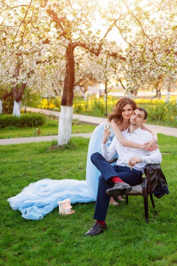 Bräutigam und Braut zusammen, Paare heiratend Junge Paare, die in blühendem Frühlingsgarten umfassen Liebe und romantisches Thema stockfoto