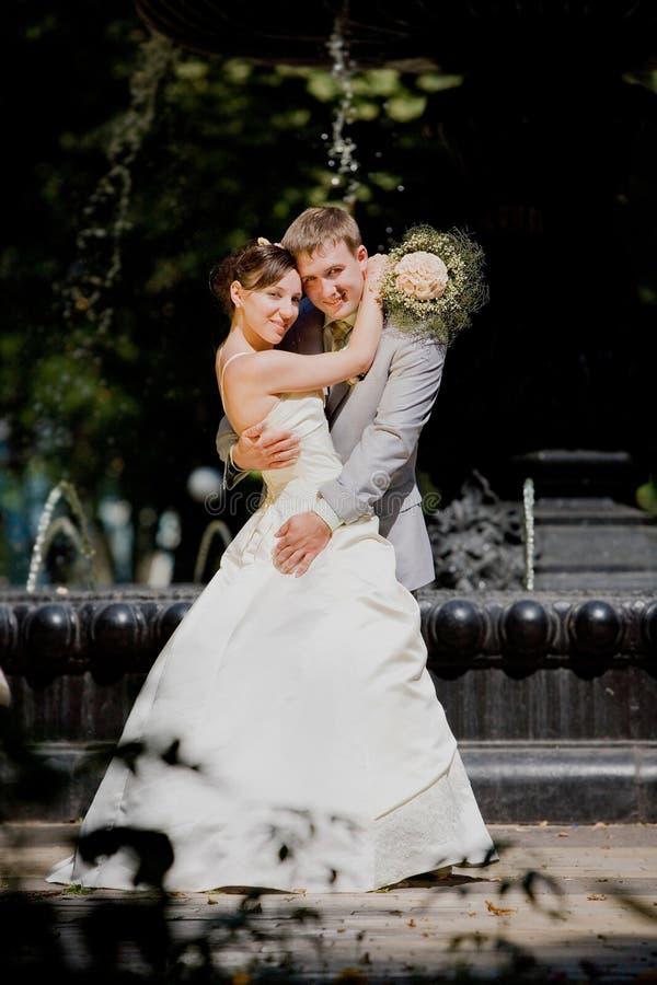 Bräutigam- und Brautfreude gegen Hintergrundbrunnen lizenzfreie stockbilder