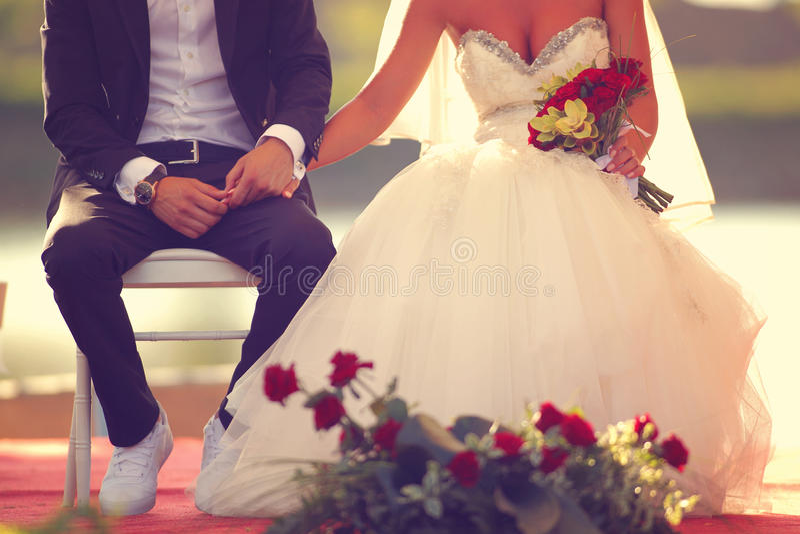 Bräutigam und Brautsitzen und -Händchenhalten stockbilder