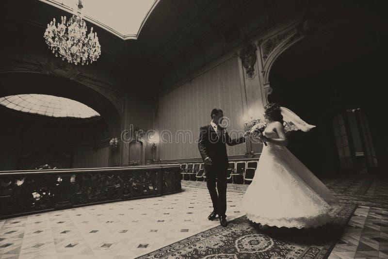 Bräutigam wirbelt eine Braut in der Mitte der alten Halle lizenzfreies stockbild