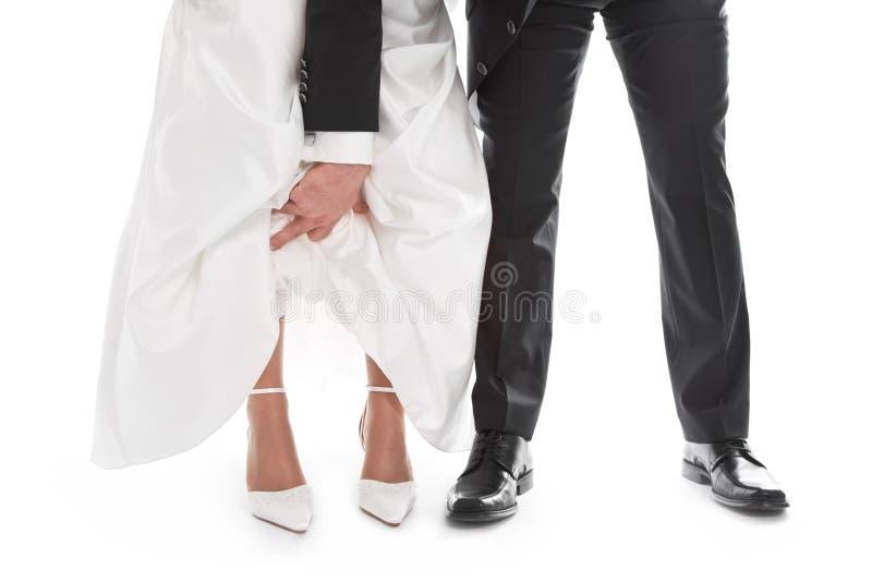 Bräutigam zeigt die Füße der Braut, Schuh, Kleid - Hochzeit, Heirat. lizenzfreies stockfoto