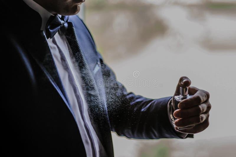 Bräutigamgebrauchsparfüm des jungen Mannes mit sichtbaren Tropfen stockbild