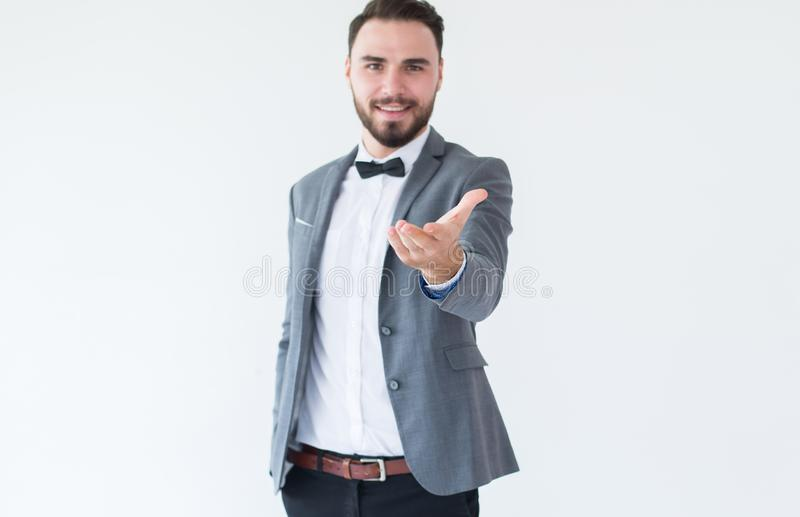 Bräutigamgut aussehender mann mit bärtigem in formalem Smokings- und Klagenvertretungshandgruß und -willkommen auf weißem Hinterg lizenzfreie stockbilder