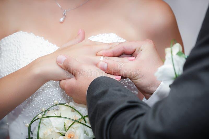 Bräutigamjungvermählten trägt Ringbraut an einem Hochzeitspaar lizenzfreies stockbild