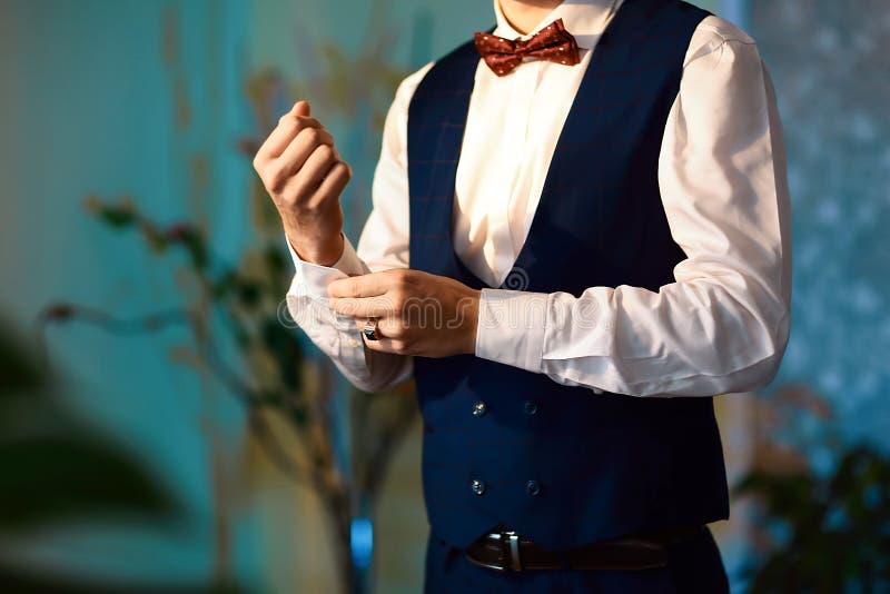 Bräutigammorgenvorbereitung, hübscher Bräutigam, der angekleidet erhält und für die Hochzeit, tragende Manschettenknöpfe sich vor lizenzfreies stockbild