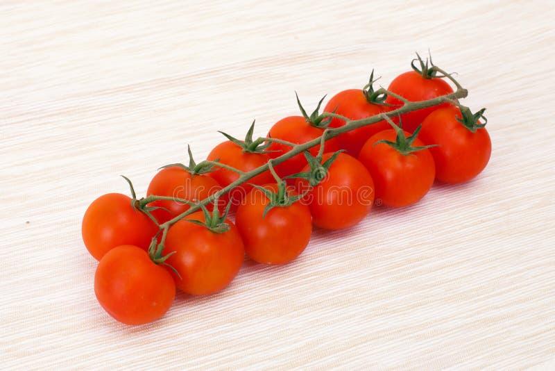 Bråckbandet om körsbärsröda tomater arkivbilder