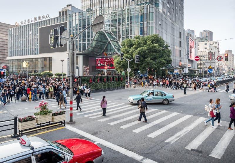 Brådska av folk på genomskärningen av Henan den mellersta vägen och den fot- gatan för Nanjing väg, Shanghai, Kina arkivbild