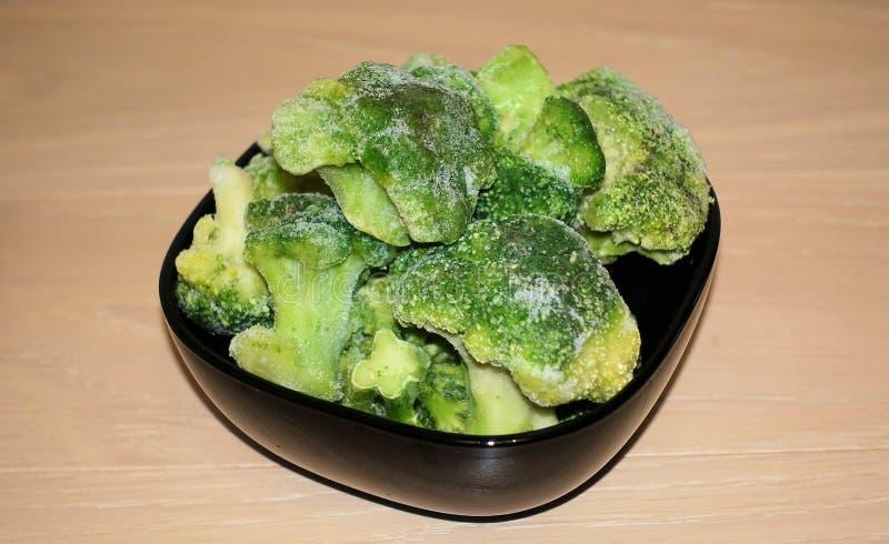 Brócolis congelados frescos em uma placa preta, alimento saudável, close up fotografia de stock royalty free