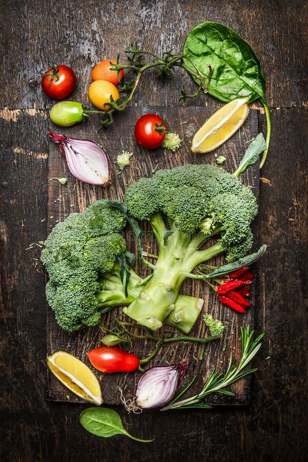 Brócolis e ingredientes e tempero frescos dos vegetais para o vegetariano saboroso que cozinha no fundo de madeira rústico, vista imagem de stock