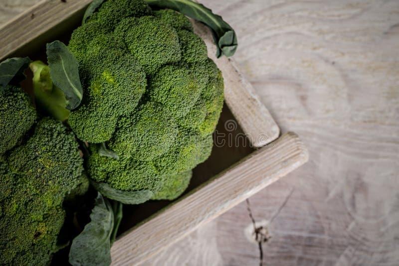 Brócolis frescos em tigela sobre mesa de madeira, próximos imagem de stock royalty free