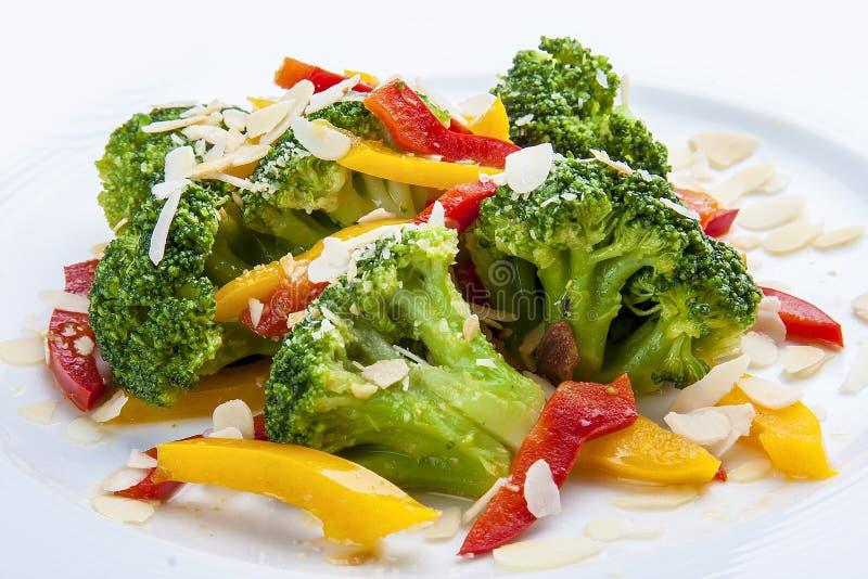 Bróculi dietético con las verduras y los cacahuetes En una placa blanca foto de archivo libre de regalías
