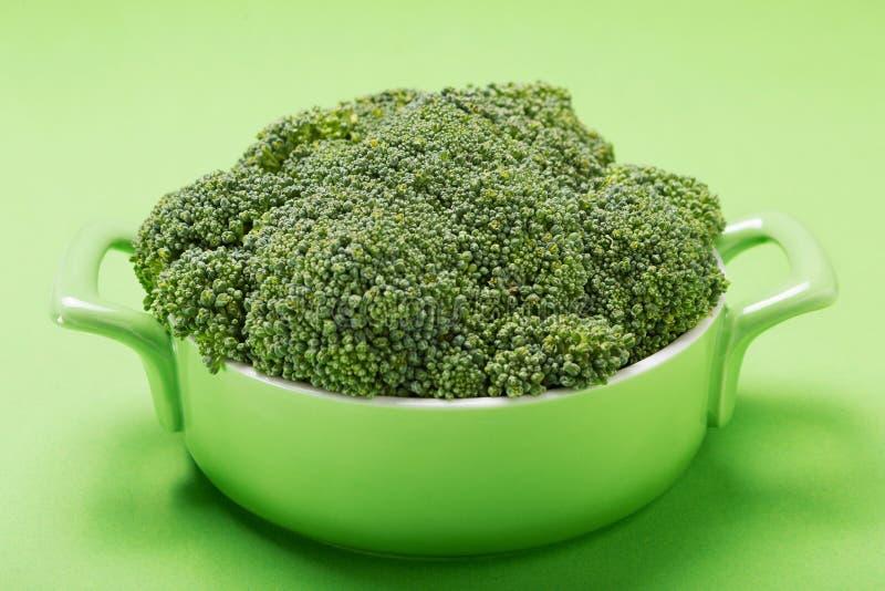 Bróculi en una cacerola verde, en un fondo verde, comida sana fotos de archivo