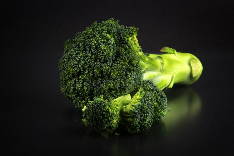 Bróculi fresco con un fondo negro imagen de archivo
