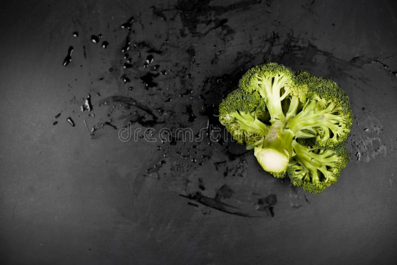 Bróculi mojado verde fresco en fondo negro imagenes de archivo
