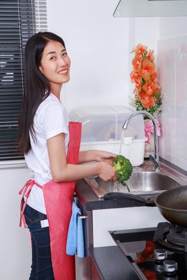 Bróculi que se lava de la mujer debajo de la agua corriente en el fregadero de cocina imagen de archivo