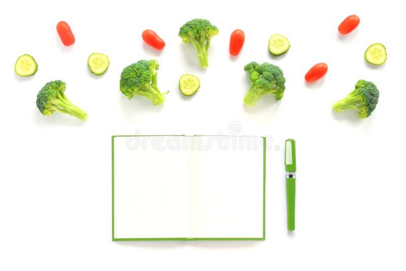 Bróculi, tomates y composición de los pepinos con el cuaderno verde fotografía de archivo