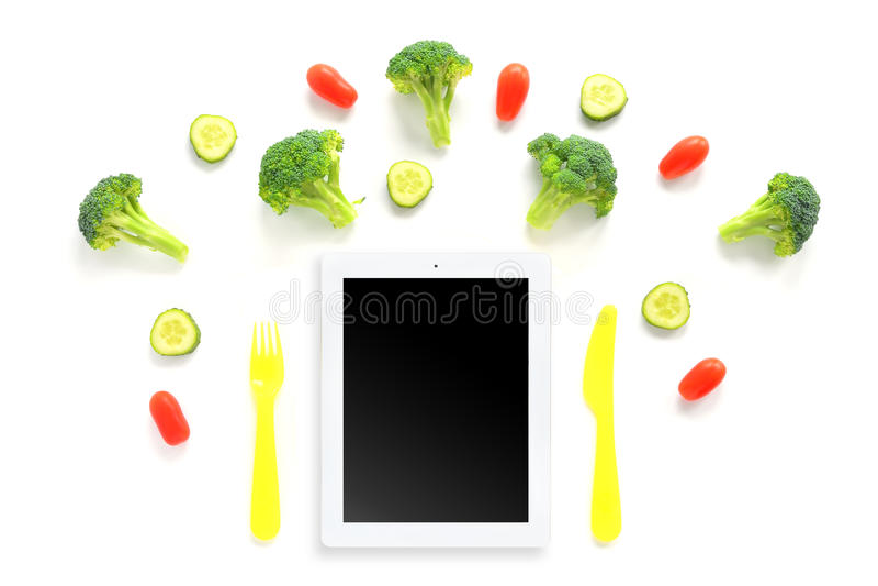 Bróculi, tomates y composición de los pepinos con la tableta fotografía de archivo libre de regalías