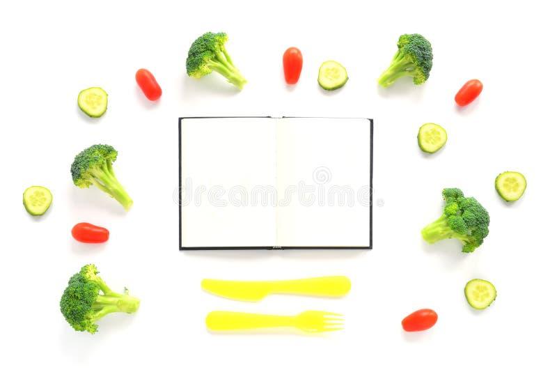 Bróculi, tomates y composición de los pepinos con los cubiertos y el cuaderno fotografía de archivo