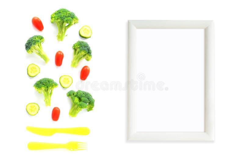 Bróculi, tomates y composición de los pepinos con los cubiertos y el marco imagen de archivo libre de regalías
