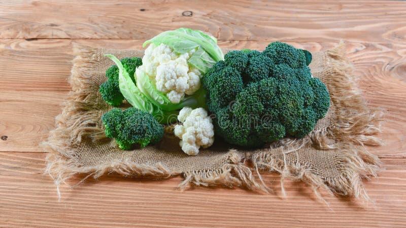 Bróculi y coliflor frescos en el paño viejo, en viejo fondo de madera Concepto local de la producción de la cosecha estacional de fotografía de archivo