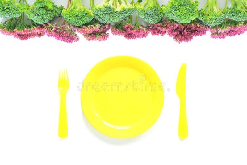 Bróculi y composición de las flores con la placa fotos de archivo