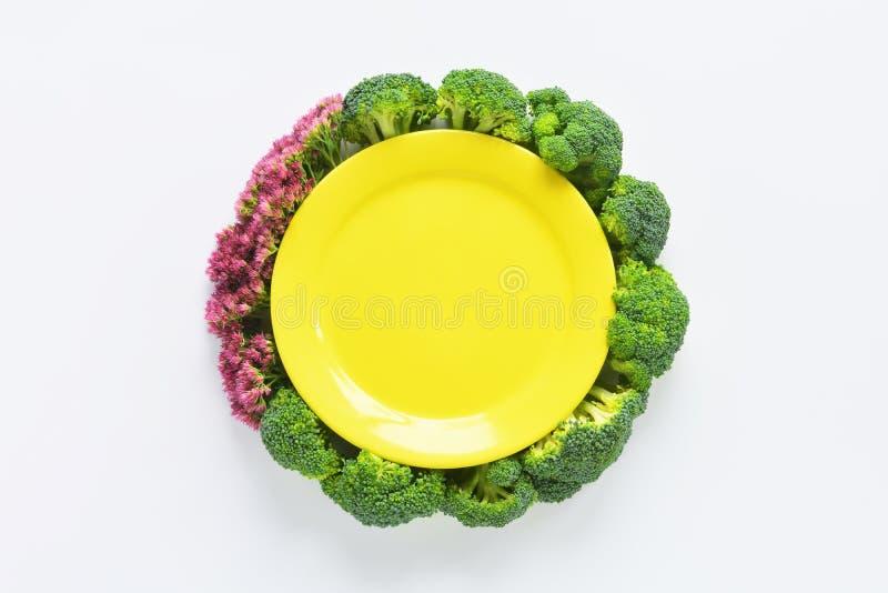 Bróculi y composición redonda de las flores con la placa foto de archivo libre de regalías