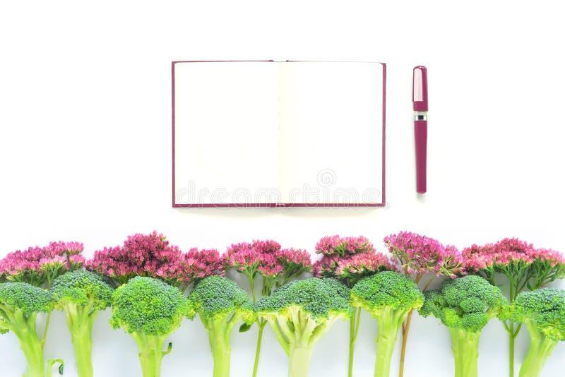 Bróculi y frontera de las flores con el cuaderno fotos de archivo