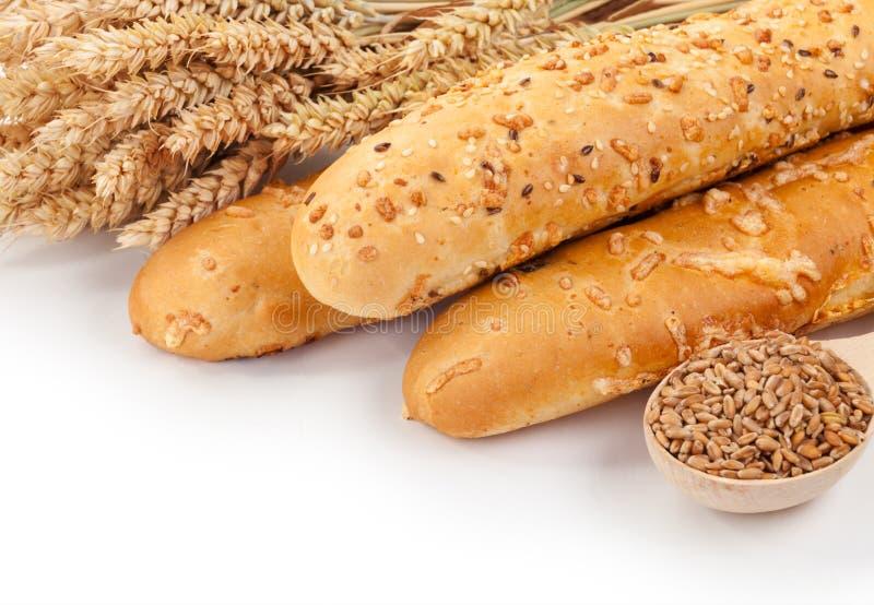 Bröd, öron och korn av vete på en vit bakgrundsisolering arkivfoto