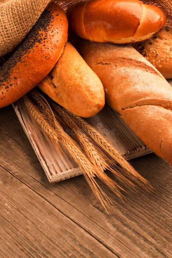 Bröd bagett, släntrar och bullar på träskrivbordet vertikalt arkivfoton