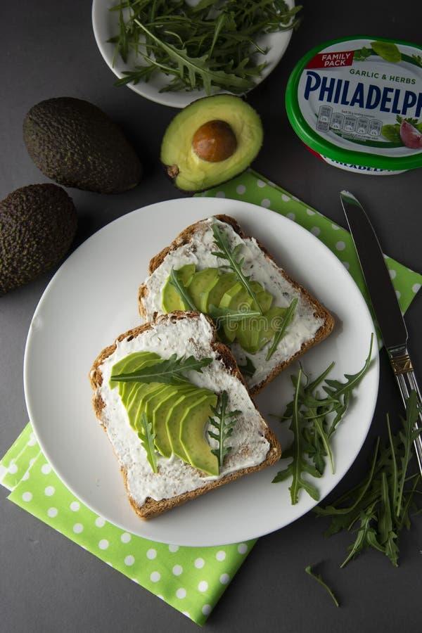 Bröd för avokadosmörgåsrostat bröd gjorde med den nya skivade avokadot, gräddost sund begreppsmat Grå färgbakgrund Mat frukost arkivbilder