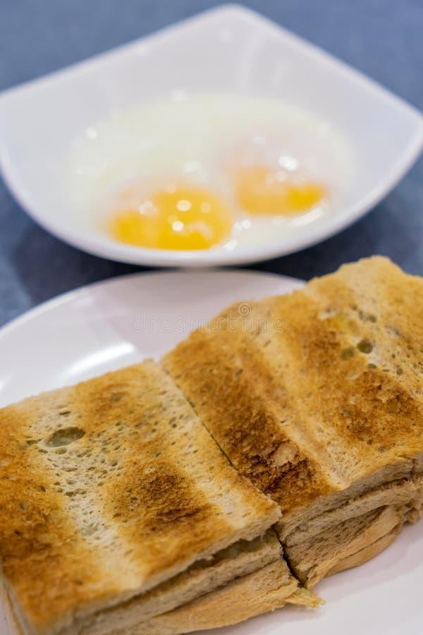 Bröd för den Singapore frukosten Kaya Toast, kaffeoch halvan kokade ägget fotografering för bildbyråer