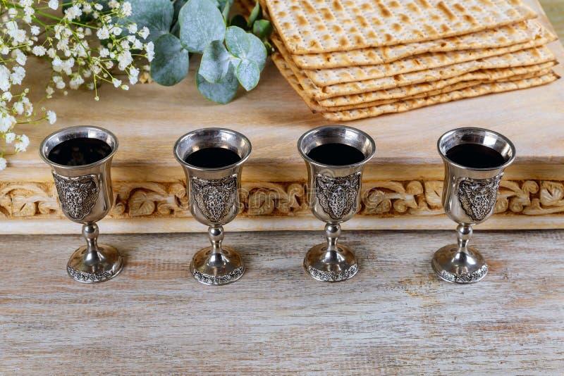 Bröd för ferie för påskhögtidmatzoh judiskt, fyra exponeringsglas koschert vin över trätabellen arkivfoton