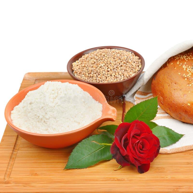 Bröd, helt korn och mjöl som isoleras på vit bakgrund arkivfoton