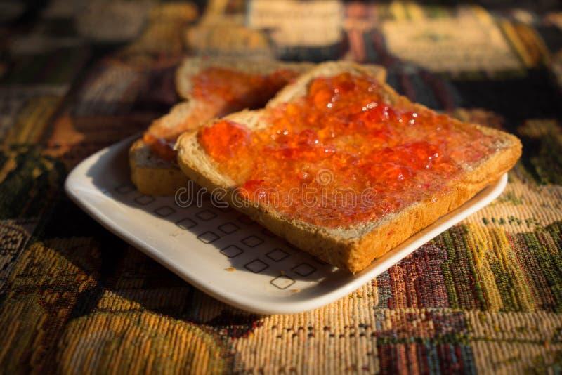Bröd med jordgubbedriftstopp på den vita plattan i morgon arkivfoton
