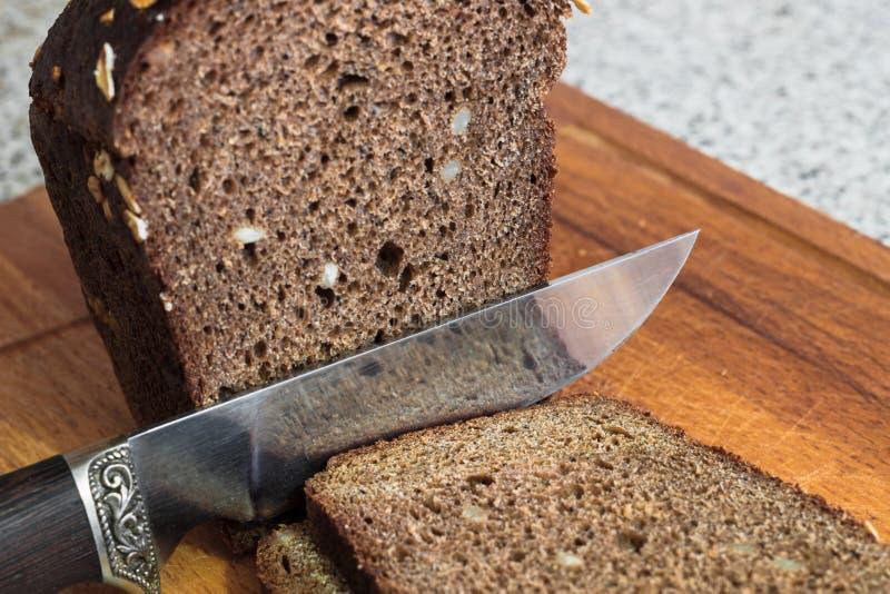 Bröd med muttrar och en inristad kniv fotografering för bildbyråer