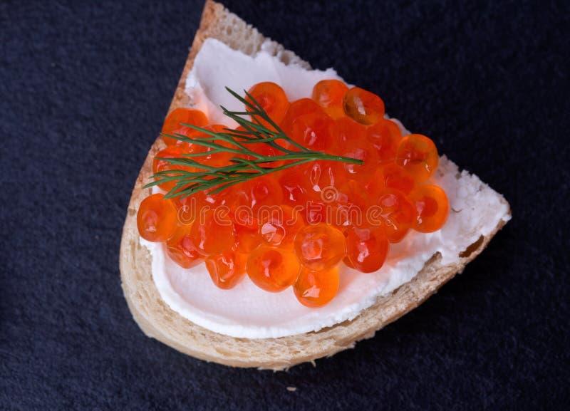Bröd med ny gräddost och den röda kaviaren royaltyfri foto