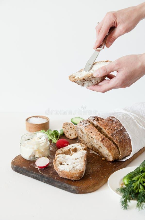 Bröd med salt, smör, gurkan och rädisor ligger på en vit bakgrund En flicka breder smör på en smörgås arkivfoto
