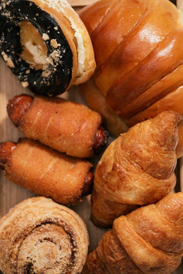 Bröd med torkade frukter och en andra olika typer av nya gjorda bröd som tjänas som på trämagasinet royaltyfri fotografi