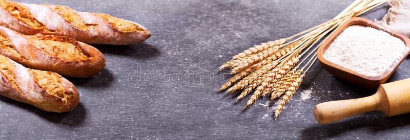 Bröd med veteöron och bunken av mjöl royaltyfri foto