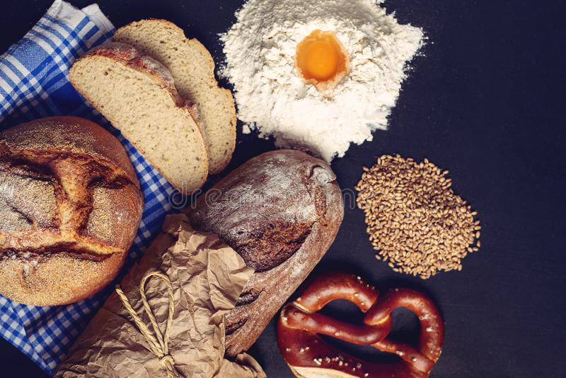 Bröd och bagetten slogg in i ett papper som var klart för kunder och något mjöl med ett ägg - Bild royaltyfri bild