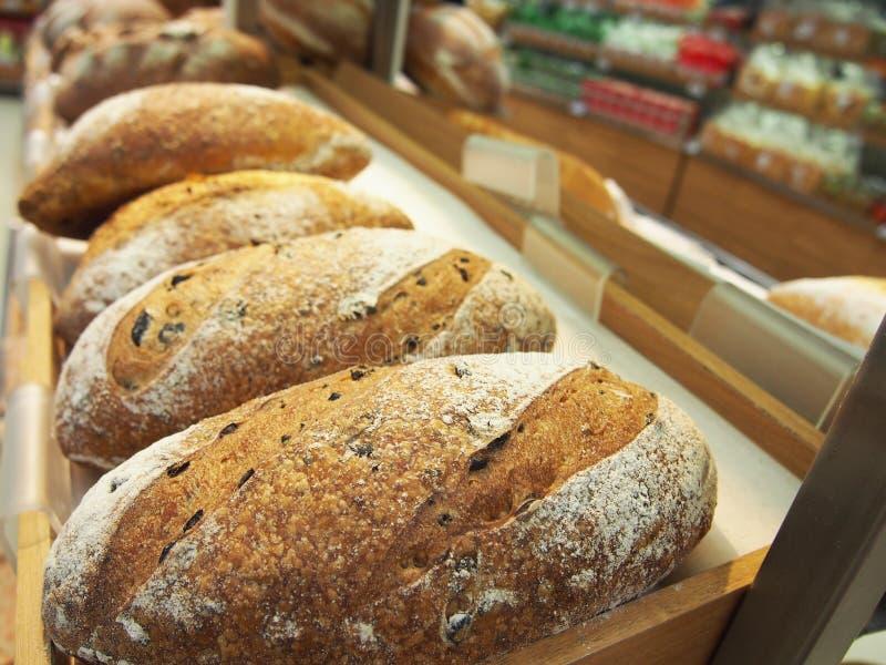 Bröd och bullar in på hylla i bageri- eller bagare` s shoppar arkivfoto