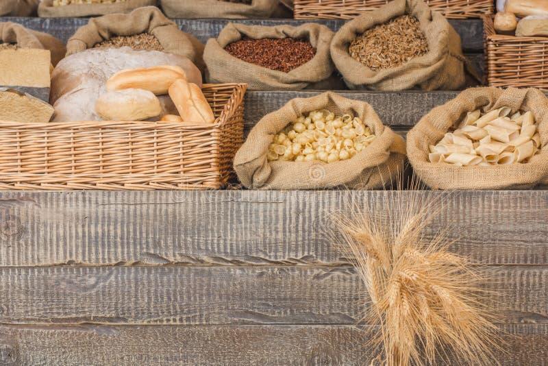 Bröd- och pastagrupp på en lantlig träworktop med kopieringsutrymme, sunt ätabegrepp royaltyfri bild