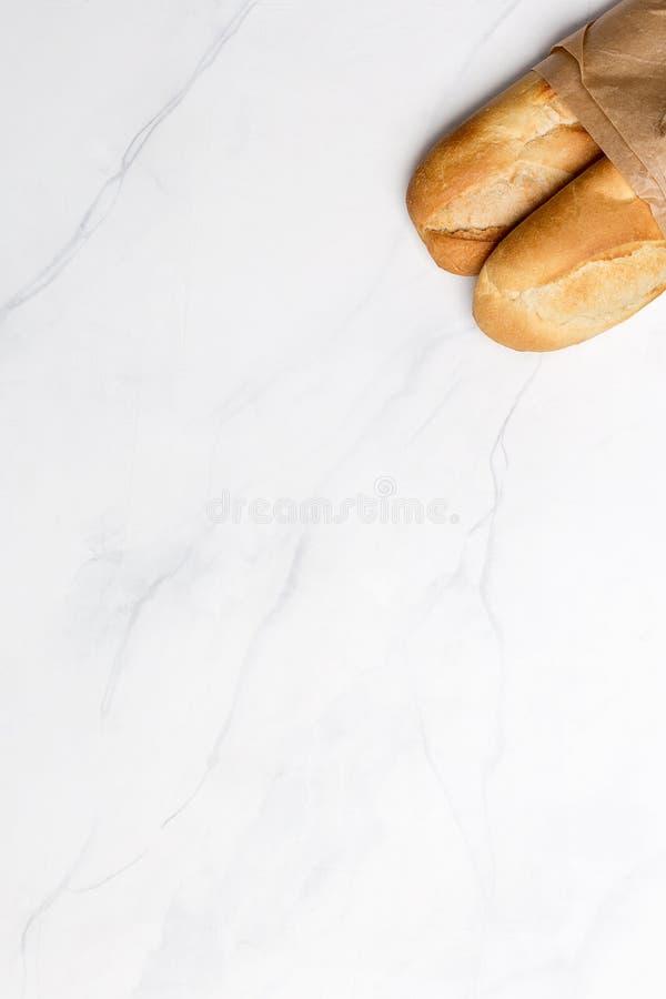 Bröd på baner med vit marmorerar bakgrund royaltyfria bilder